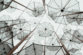 Many transparent umbrellas under a grey sky
