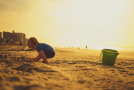 A child playing on the beach under the sun