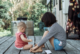 Baby with older girl playing on a porch