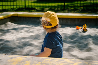 Kid playing in a sunny playground wearing a yellow cap