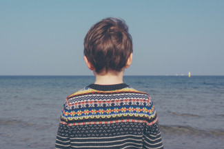 Boy with a sweater looking at the sea