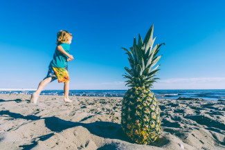 Kid on the beach and a pineapple on the sand