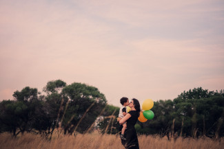 Mum and son kissing each other on a field and holding balloons